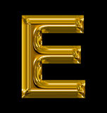 Letter E rounded shiny golden isolated on black. Background Royalty Free Stock Photography