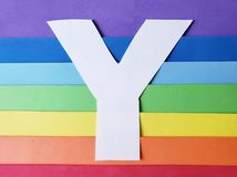 Letter E in white with background in rainbow colors. Backdrop for ads related to colors and lgbt community, graphic sign of a writing system with multicolor stock photo