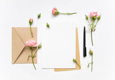 Letter and eco paper envelope on white background. Invitation cards, or love letter with pink roses. Holiday concept, top view, fl. Flat lay shot of letter and Royalty Free Stock Photos