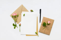 Letter, envelope and gift on white background. Invitation cards, or love letter with pink roses. Holiday concept, top view, flat l Stock Images
