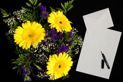 Letter and flower. Letter, envelope and pen with a bouquet of flowers an black background stock photography
