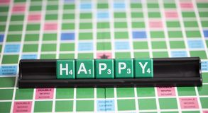 Letter green scrabble is spelling word HAPPY on the rack. It is the emotional felling stock images