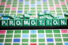 Letter green scrabble is spelling word PROMOTION on the rack. Letter green scrabble is spelling word PROMOTION. Promotion is a very important component of stock image
