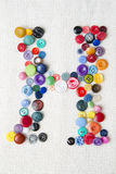 Letter H of the alphabet of buttons of various shapes and colors Stock Images