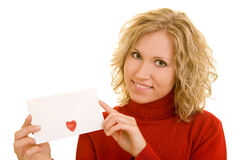 Letter with heart. Blonde woman showing a letter with a heart-shaped sticker on it stock photos