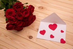 Letter with hearts and a bouquet of red roses on wooden backgrou Royalty Free Stock Photos
