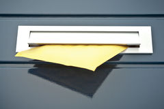 Letter in a home mailbox. Closeup image of a front door built-in mailbox with a yellow parcel or letter partially in it stock photography