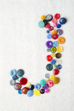 Letter J of the alphabet of buttons of various shapes and colors Royalty Free Stock Image