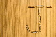 Letter J of paper clip on a wooden brown floor. Letter J of paper clip on a wooden brown floor background for top view Stock Images