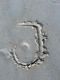 Letter J. Written on a sand on the beach - may be used for any kind of design as a background or an element. Also as a type, typeface or handwritten font Stock Photo