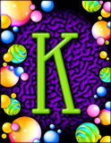 Letter K. Green letter K on a purple background with colorful spherical designs as a border Stock Images