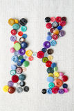Letter K of the alphabet of buttons of various shapes and colors Stock Photo