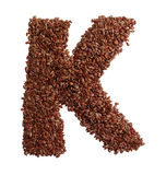 Letter K made with Linseed also known as flaxseed isolated on wh Stock Photos