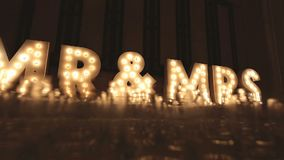 Letter light box with text Mr & Mrs retro theater style on backdrop decoration in wedding reception dinner party, Dolly slide shot stock video footage