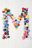 Letter M of the alphabet of buttons of various shapes and colors Royalty Free Stock Photography