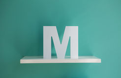 Letter M turquoise color on a white shelf Royalty Free Stock Image