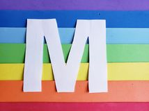 Letter M in white with background in rainbow colors. Backdrop for ads related to colors and lgbt community, graphic sign of a writing system with multicolor royalty free stock images