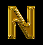 Letter N rounded shiny golden isolated on black. Background Royalty Free Stock Photos