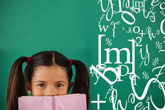 Composite image of letter and number jumble. Letter and number jumble against schoolgirl hiding behind a book against green background Stock Image