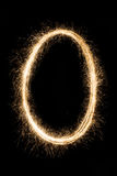 Letter or number null O from sparklers alphabet on black Royalty Free Stock Photo