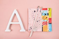 Letter A and paintbrushes on a colorful plate stock photo
