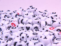 Letter pearls. Beads with the alphabet printed on them Stock Photography