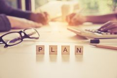 The letter `PLAN` is on the table with business people working behind the scenes - Business team collaboration ideas. Stock Photos