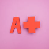 Letter A with plus sign. On pink background royalty free stock photos