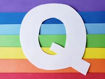 Letter Q in white with background in rainbow colors. Backdrop for ads related to colors and lgbt community, graphic sign of a writing system with multicolor royalty free stock photos