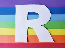 Letter R in white with background in rainbow colors. Backdrop for ads related to colors and lgbt community, graphic sign of a writing system with multicolor stock photos