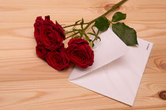 Letter and red roses on wooden background Royalty Free Stock Photos
