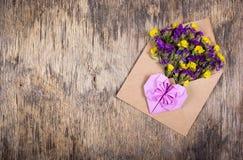 letter romantiker Blommor i ett pappers- kuvert och en pappers- hjärta av origami Royaltyfria Bilder