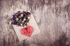 letter romantiker Lösa blommor och en pappers- hjärta Hjärta av origami Arkivbild