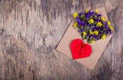letter romantiker Torka blommor i ett pappers- kuvert och hjärtan av origami Bakgrunder och mallar kopiera avstånd Royaltyfri Bild