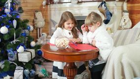 Letter for Santa Claus, two girls, sisters write and draw, girls sit near the fireplace, children in the house near. Christmas tree, letter to Santa in stock video