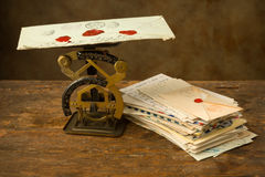 Letter scale and old letters. Antique letter scale on an old wooden table with a bundle of letters Stock Images