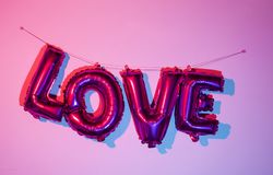 Letter-shaped balloons forming the word love. Some fuchsia letter-shaped balloons forming the word love hanging on a pink wall, with a stereoscopic effect Stock Photography
