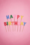 Letter-shaped happy birthday candles on pink Royalty Free Stock Image