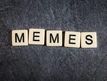 Letter tiles on black slate background spelling Memes. Tiles on black slate background spelling Memes stock photo