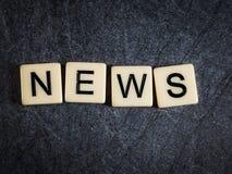 Letter tiles on black slate background spelling News stock photo
