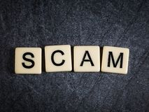Letter tiles on black slate background spelling Scam royalty free stock photography