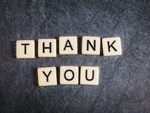 Letter tiles on black slate background spelling Thank You. Tiles on black slate background spelling Thank You stock photos