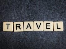 Letter tiles on black slate background spelling Travel. Tiles on black slate background spelling Travel stock photo