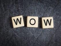 Letter tiles on black slate background spelling Wow. Tiles on black slate background spelling Wow stock images