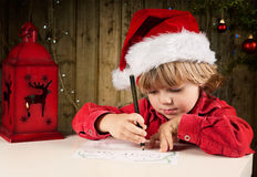 Letter to Santa. Blond boy writes a letter to Santa Royalty Free Stock Photo