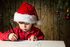 Letter to Santa. Blond boy writes a letter to Santa Royalty Free Stock Photos