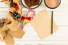 Letter to Santa Claus concept on white wooden table. With hot chocolate, brown cake, winter holiday decorations and sugar cane candy Stock Photography