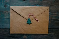 letter to Santa Claus, envelope with wooden Christmas decor in the form of wax seal, flat lay on dark wooden background royalty free stock image