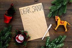 Letter to Santa Claus template. Mockup on craft paper with text Dear Santa near New Year decoration like fir branches. Candle, toy horse on dark wooden stock photo