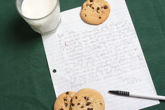 Letter to Santa Clause. Little kid Letter to Santa Clause ask for gifts. On a hunter green table cloth with cookies and milk Royalty Free Stock Images